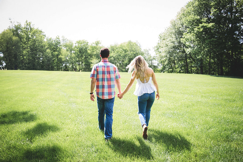 Man & woman holding hands in a park